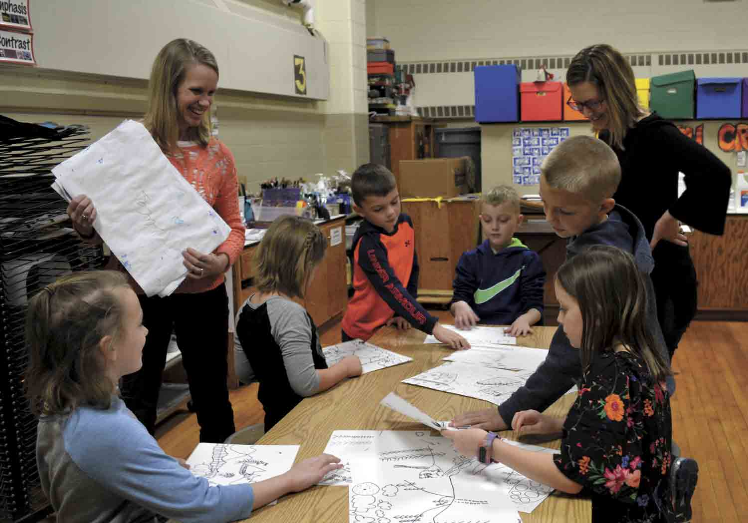 Local art teachers Mina Fantz and Annie Adams (l-r) work with North Fayette Elementary first- and second-graders (l-r) Mikah Opperman, Eva Sayer, Max McElree, Kypton McGrane, Eli Novak and Sophia Gardner on an art project. The instructors just recently connected the young artists of North...