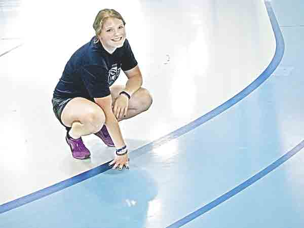 Bridgett Madden, an Upper Iowa University senior majoring in mortuary science and a member of the track team, pauses during a workout Thursday at the UIU Recreation Center. The surface of the indoor track at her fingertips is slated to be replaced with one competitive runners can use spikes...