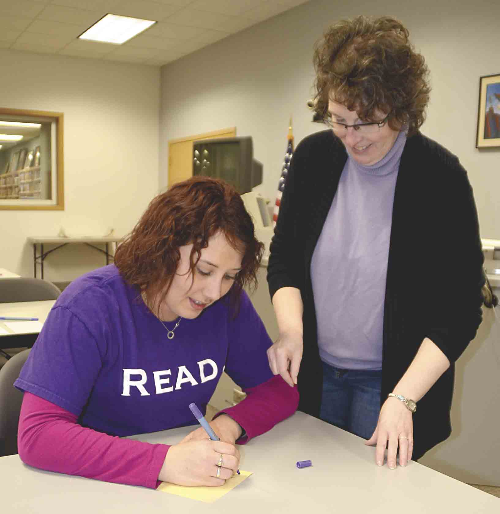 "On Tuesday, Jan. 23, Annette Butikofer (right), Fayette Community Library director, shows her employee, Michelle Whitlock, how to write with a calligraphy pen during the class Butikofer was teaching entitled ""Calligraphy: The History and Practice."" (Chris DeBack photo..."