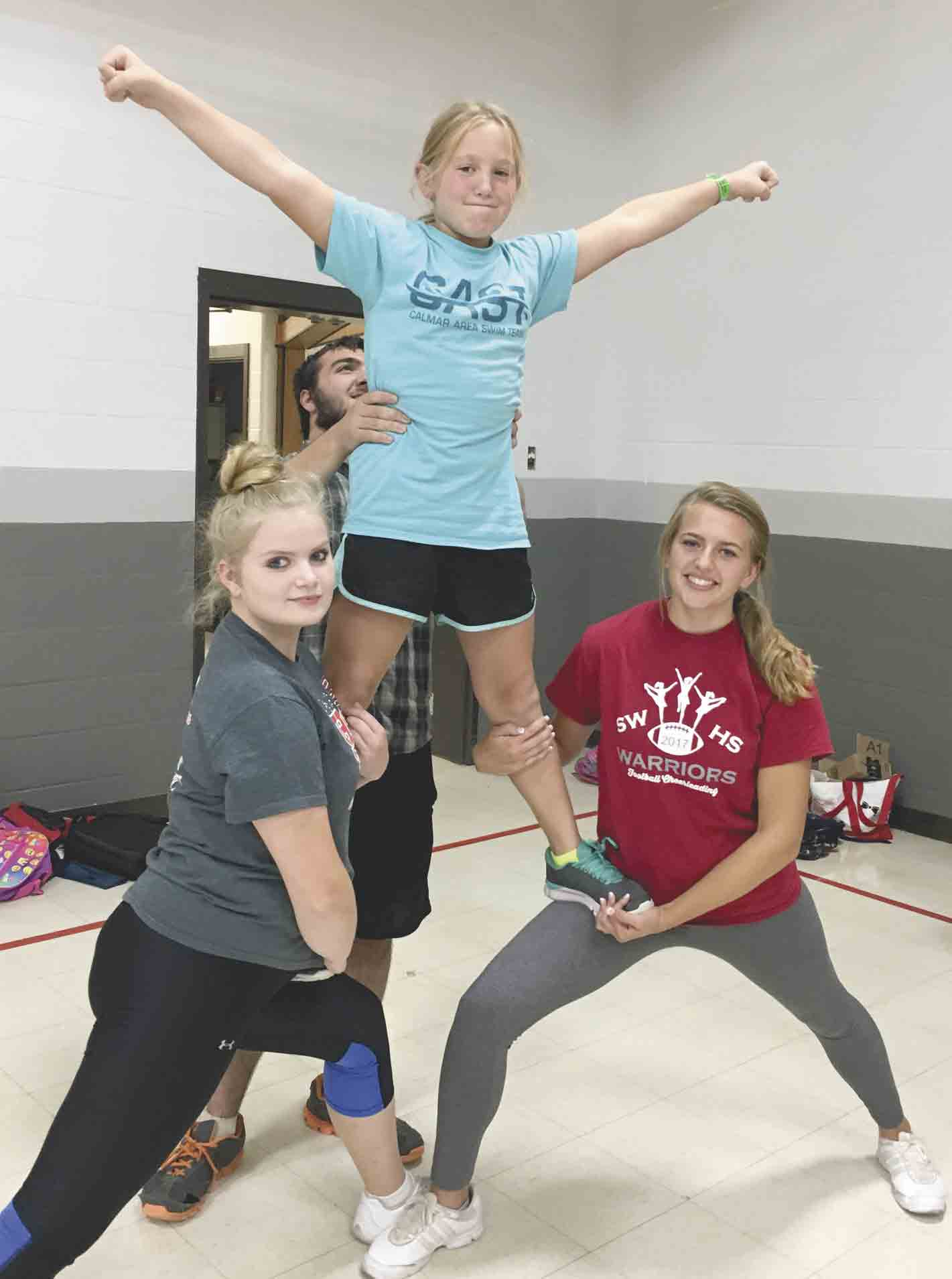 South Winn senior Hanna Schmitt (right) and fellow cheerleaders Anna-Brit Lien and Wyatt Trezona (back) help teach Junior Warriors CHEER participant Autumn Schmitt (top) a stunt. The youth cheerleading program was created by Hanna and helps teach much more than cheerleading. (submitted...