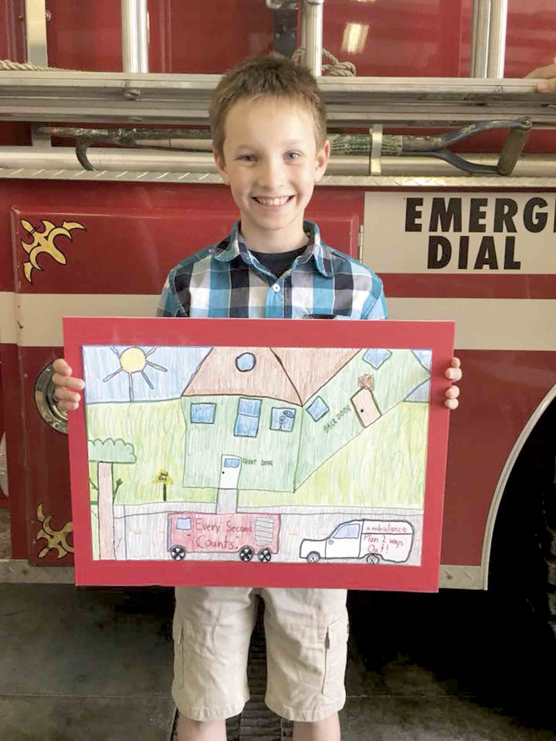 """West Union Elementary third-grader Keegan Weidemann proudly shows off his Fire Pevention Week poster, which took second place in the statewide contest. His poster, which illustrates this years theme of """"Every Second Counts: Plan Two Ways Out!"""" will be displayed in the Iowa..."""