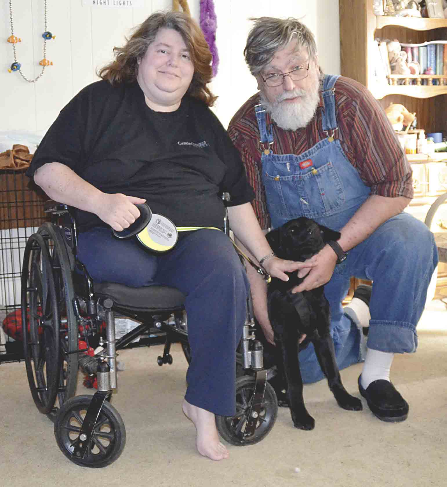Michelle and Jim Morse (l-r) pet their new puppy Gibbs that Michelle got as an emotional support animal after having her left leg amputated a while ago due to DTV blood clots. The family's furnace's exhaust pipe was blocked by snow on the morning of Feb. 5. Gibbs was being...