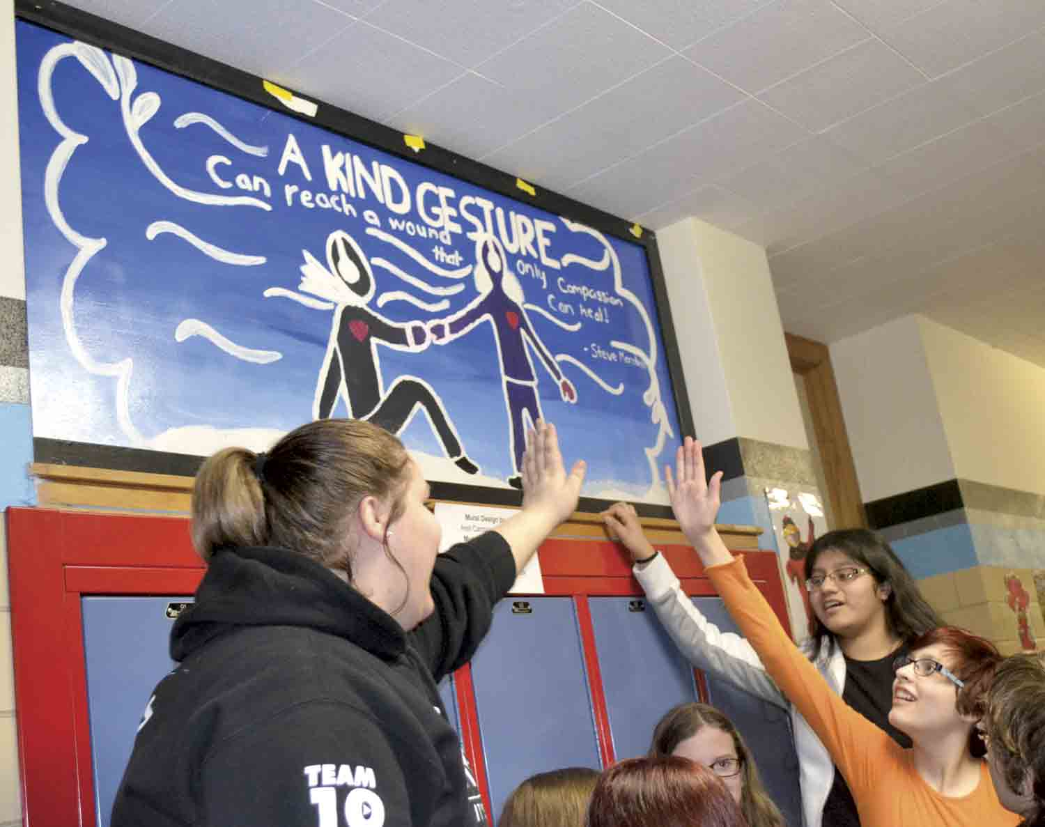 During last week's unveiling at North Fayette Valley Middle School, Cassidy Mohler, Areli Campos-Morales, and Sierra Kemp (clockwise from left) give a high-five as they unveil their original mural, which was designed by Campos-Morales. Many of the 12 student-created murals had themes...