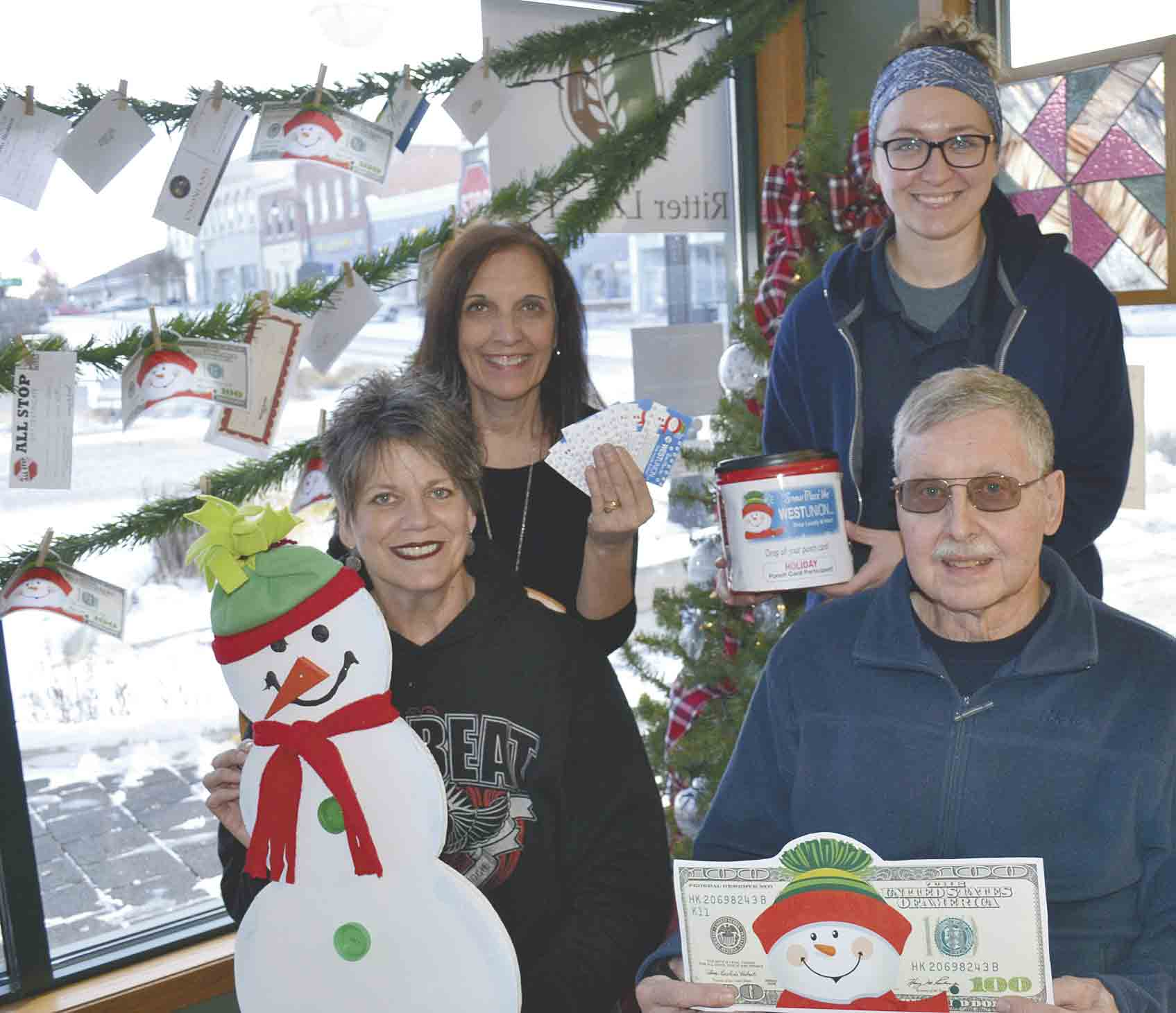 Area shoppers are invited to join the jovial snowman as well as area business owners, including (l-r) Ken Popenhagen, Chelsey Matthias and Kaleb Vagts in taking part in a variety of area promotions as they shop West Union throughout the holiday season for a variety of great deals and fun prizes....