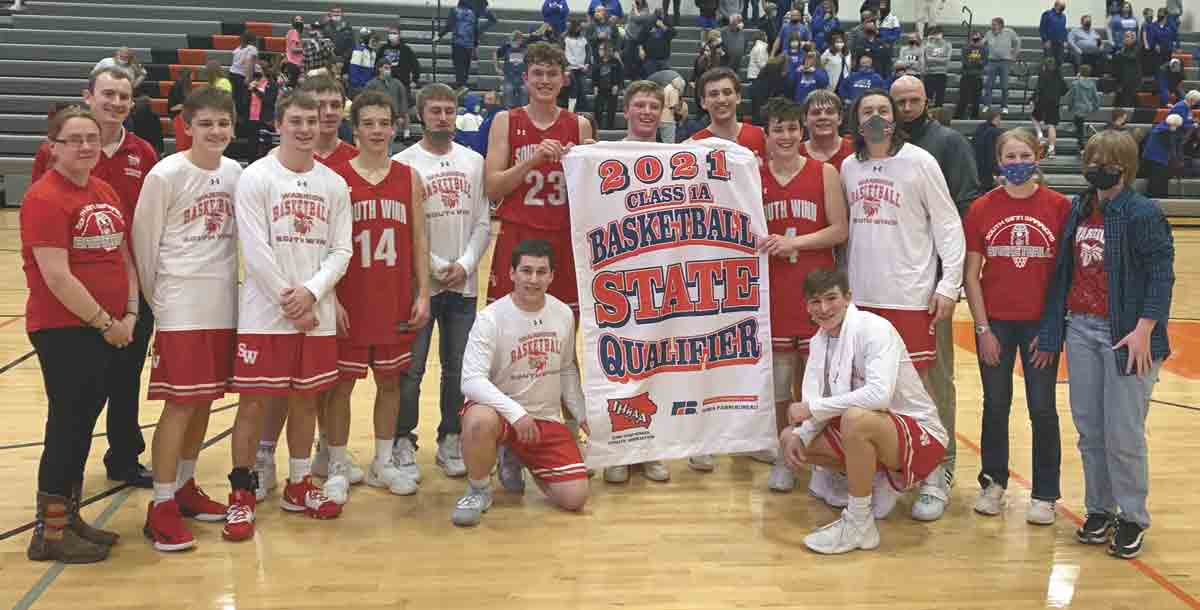 The South Winneshiek boys' basketball program, including players, coaches, and managers, celebrates with its newly earned State qualifier banner. The Warriors downed a talented Gladbrook-Reinbeck squad on Saturday night in Manchester, giving the team its first State appearance since 1987. (...