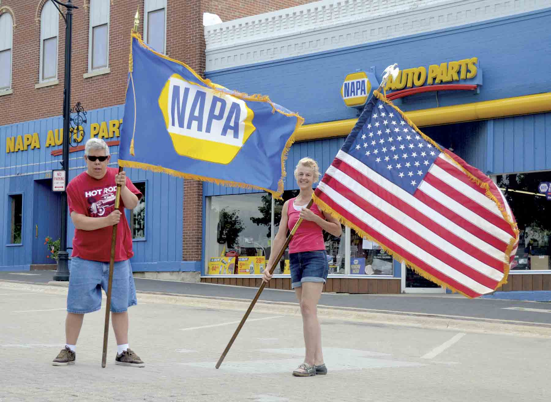 Chris Kleppe of West Union and business owner Joni Spies (l-r) fly the flags high in preparation for the Sixth Annual Block Party, which will be held in downtown West Union on Flag Day, Thursday, June 14. The annual event, which started after the Downtown Streetscape Project finished six...