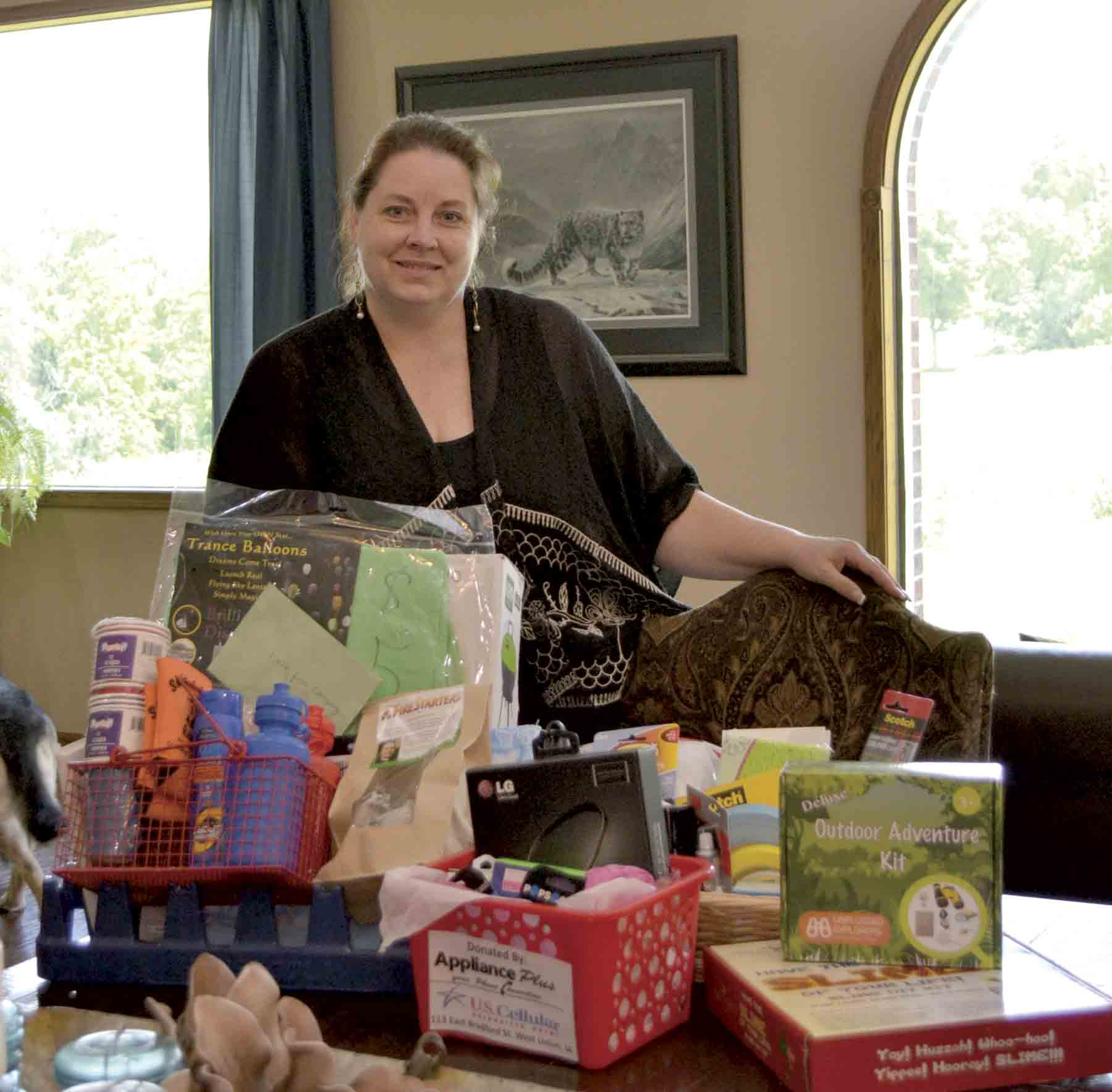 Clermont Community Club member Tracy Johnson stands with just a few of the items that will be available during the silent auction at the Third Annual Clermont BBQ in the Park on Monday, July 16. In addition to the auction, which includes prizes such as gift certificates to local...