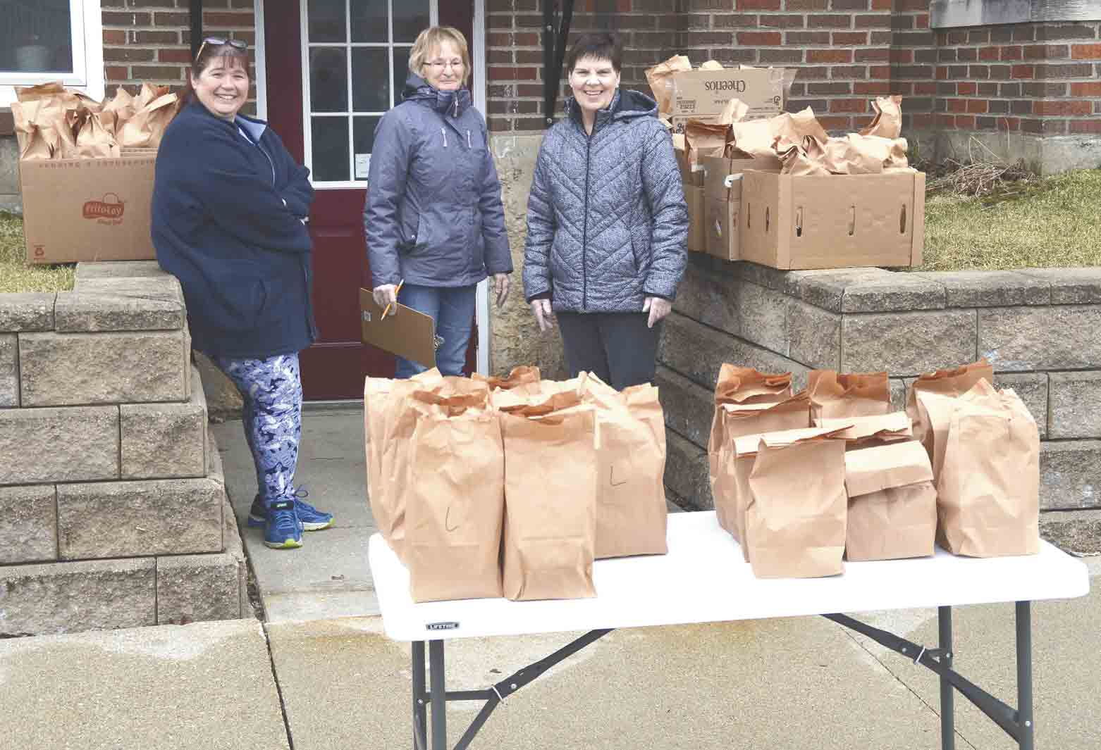North Fayette Valley School Lunch personnel (l-r) Tina Berg, Sheila Noska, and Gloria Wagner were helping deliver sack lunches Monday, March 23, at the Bethel Presbyterian Church in West Union. (Jack Swanson photo) 	Schools out for now, but that doesn't mean students have to go...